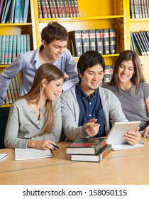 Happy multiethnic students with digital tablet discussing in college library