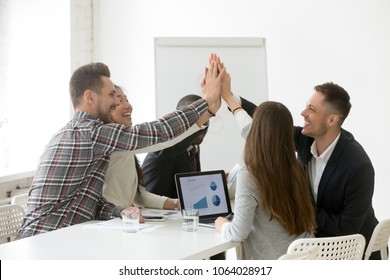 Happy multi-ethnic team giving high five together promising loyalty engagement, diverse partners group join hands celebrating victory, great result, corporate success, good relations, unity concept