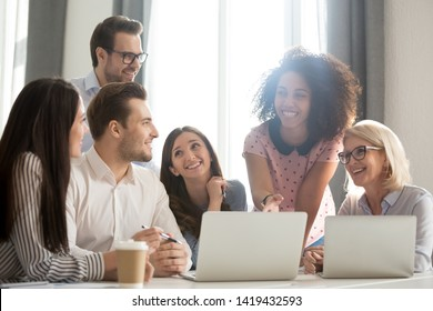 Happy multiethnic work group sit at office desk discussing business idea using laptop, smiling diverse employees brainstorm busy at computer, laugh talking negotiating together at casual meeting