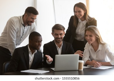 Happy multiethnic young businesspeople sit at office desk look at laptop cooperating on shared work project, smiling diverse colleagues using computer watch webinar online coworking at meeting