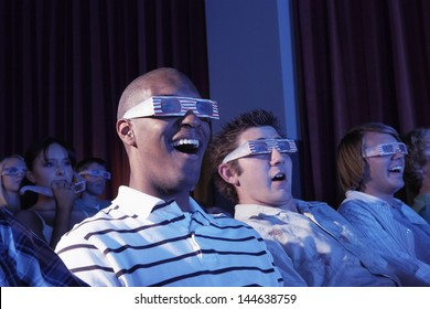 Happy multiethnic young men watching a 3-D movie in the theatre