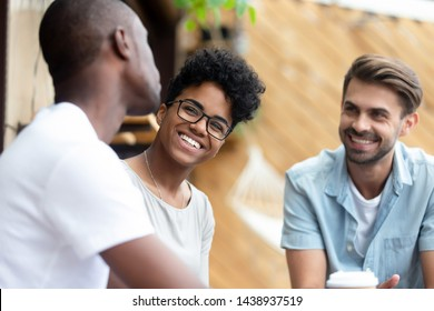 Happy multiethnic young people relax together have fun talking and chatting sharing ideas, smiling multiethnic diverse friends speak resting hanging out in coffeeshop. Communication concept