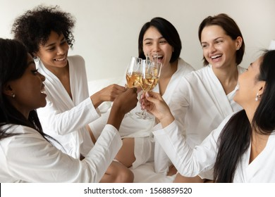 Happy multiethnic young women best friends wear bathrobe clink glasses together sit on bed, smiling girls bride and bridesmaids drink champagne laugh celebrate bachelorette spa party in hotel concept