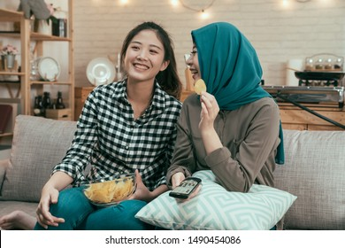 Happy multiethnic young women sitting on couch and watching funny movie on tv. asian girl roommates laughing with comedy playing on television and eating junk food in home kitchen on weekends.