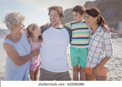 Happy multi-generated family at beach during sunny day