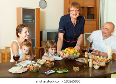 Happy multigeneration family with chicken at home interior