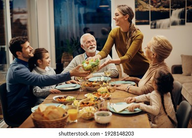 Happy multi-generation family enjoying in a lunch together at home. Focus is on young woman serving salad at dining table.  - Shutterstock ID 1928148203