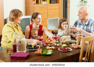 happy multigeneration family posing together over celebratory table at home