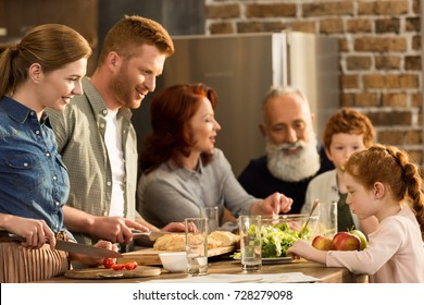 happy multigeneration family preparing dinner together in kitchen