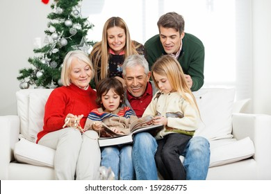 Happy multigeneration family reading book together in house