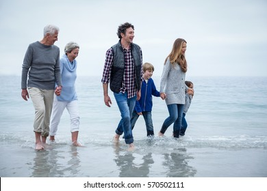Happy multi-generation family walking in shallow water at beach