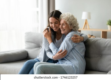 Happy multi-generational family sitting on couch in living room, elderly grandmother snuggle to grown up granddaughter, adult daughter missed mature mom, holidays, events, Mother Day congrats concept
