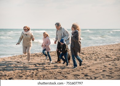 happy multigenerational family spending time together on seashore