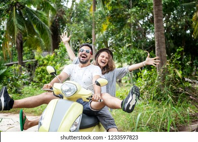 Happy multinational couple traveling on a motorbike in the jungle, honeymoon, vacation, travel concept, friends have fun