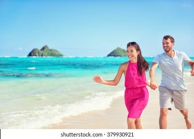 Happy multiracial Asian Caucasian couple having fun walking on perfect turquoise Lanikai Hawaii beach for summer vacation on Hawaiian island, Oahu, USA.