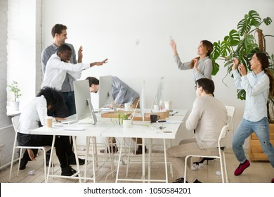 Happy multiracial business group throwing crumpled paper balls laughing having fun together in office, diverse employees doing teambuilding activity, friendly team and good relations at work concept