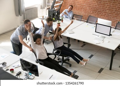 Happy multiracial colleagues group having fun together, riding on chairs in office, diverse excited office workers enjoying break, laughing, engaged activity, having funny competition top view
