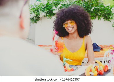 Happy multiracial couple drinking cocktails on a summer sunny day, multicultural couple and family concept