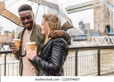 Happy multiracial couple walking in London holding an umbrella on a rainy day. Black man and white woman drinking tea or coffee, bonding and having fun together with Tower Bridge on background.