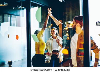 Happy multiracial crew of colleagues satisfied of completing project together giving high five, young team on millennial students celebrating success  in coworking office, team building concept
