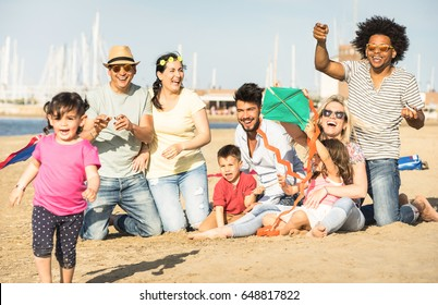 Happy multiracial families and children playing together with kite at beach vacation - Multicultural summer joy concept with mixed race people having candid genuine fun  - Warm afternoon color tones