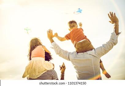 Happy multiracial families group with parents and children playing with kite at beach vacation - Summer joy concept with mixed race people having fun together at sunset  - Warm bright sunshine filter