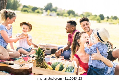 Happy multiracial families having fun with kids at picnic barbecue party - Multicultural happiness on joy and love concept with mixed race people playing with children at park - Warm bright filter
