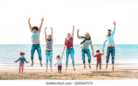Happy multiracial families jumping together at beach holding hands - Summer vacation concept with young mixed race people having genuine fun outdoors enjoying sunset - Vivid azure backlight filter