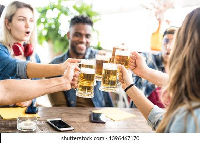 Happy multiracial friends drinking and toasting beer at brewery bar - Friendship concept with young people having fun together at cool pub restaurant - Focus on middle pint glasses - Bright filter