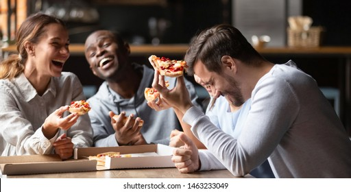 Happy multiracial friends gathering in restaurant or bar tasting sharing pizza laughing on joke, excited diverse young people have fun meeting enjoy tasty Italian food from takeaway delivery