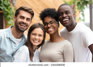 Happy multiracial friends group bonding looking at camera, young diverse people laughing having fun posing together, multi ethnic african and caucasian friendship reunion concept, head shot portrait