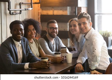 Happy multiracial friends group looking at camera having fun in cafe together, young african and caucasian people bonding sitting at coffeehouse table, smiling diverse millennial students portrait
