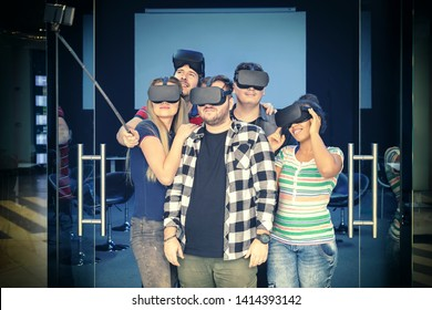 Happy multiracial friends group taking selfie playing vr glasses indoor - Virtual reality and wearable tech concept with young people having fun together with headset goggles - Generation z trends