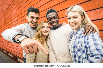Happy multiracial friends group taking selfie with mobile smart phone - Young hipster people addicted by smartphone on social network community - Lifestyle technology concept on vivid contrast filter