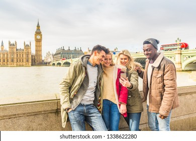 Happy multiracial friends group using smartphone in London. Mixed race millennials people lifestyle concept. Friends sharing trip on social network. Big ben and Westminster parliament on background.