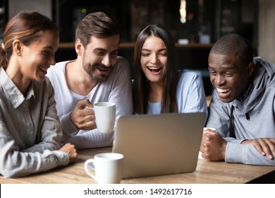 Happy multiracial friends people group looking at laptop watching funny comedy or online show together in cafe, cheerful diverse students laughing using computer drinking tea in coffee house