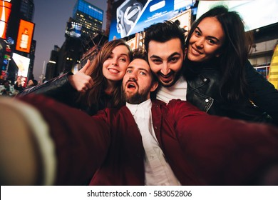 Happy multiracial friends taking selfie on Time Square, New York. Concept of students in their 20s having fun and taking pictures for travel blog.