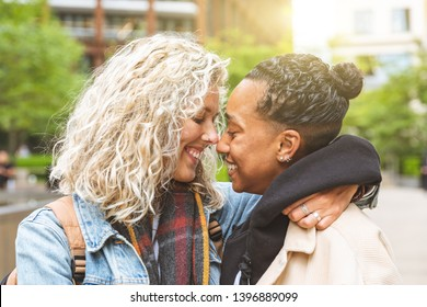 Happy multiracial girlfriends in love embracing and cuddling - Lesbian couple, millennials women, girls in London living happy lifestyle - LGBTQ concept with mixed race beautiful couple
