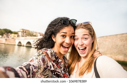 Happy multiracial girlfriends taking selfie and having fun outddors - Friendship concept with girls at spring break travel - Modern lifestyle with female best friends women - Bright day filter tone