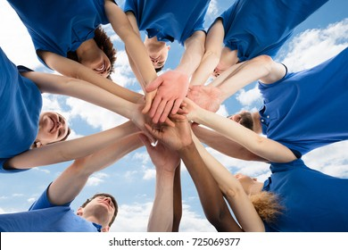 Happy Multiracial Janitors Stacking Hands Against Cloudy Sky