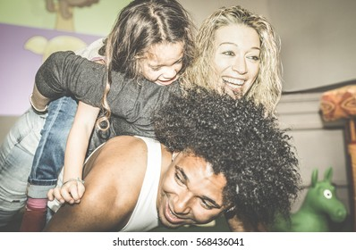 Happy multiracial mom and dad playing with mixed race daughter at kindergarten playroom - Multicultural family concept with happy child having fun with father and mother at kid toyroom - Retro filter