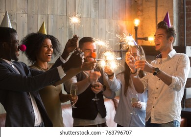 Happy multiracial people in party hats clown noses holding sparklers and champagne glasses celebrating New year eve together, excited diverse young friends having fun enjoying celebration together