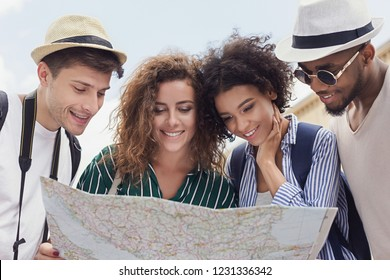 Happy multiracial travelers searching the location on city map