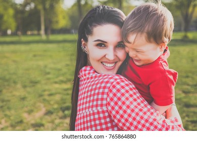 happy mum with kid smiling in the park. hipster style. casual clothes. concept of happy family