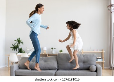 Happy mum and little daughter playing jumping on comfortable sofa in living room, mother baby sitter laughing having fun with cute kid girl at home, happy mom and child enjoy funny activity together