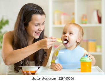 Happy mum spoon feeding child son indoor