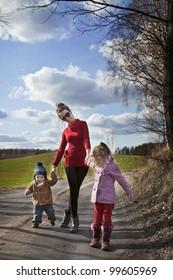 happy mum walking with her two children