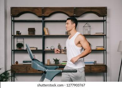 happy muscular bi-racial man running on treadmill