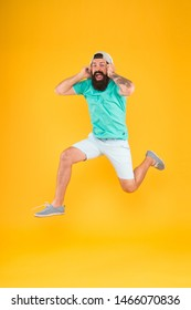 Happy music. Happy hipster jumping on music on yellow background. Bearded man enjoying song playing in headphones with smile on happy face. Happy fun and upbeat.