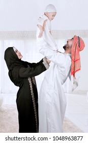 Happy muslim Arabian family with father, mother and son isolated over white